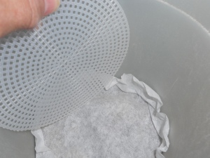 plastic canvas into bottom of planter on top of filter and rocks